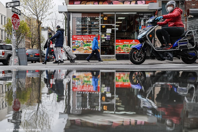 Pedestrians and a motorbike rider wear masks near a small Brooklyn deli/grocery store in April, when it was the only business open on the street. (© John Minchillo/AP Images)