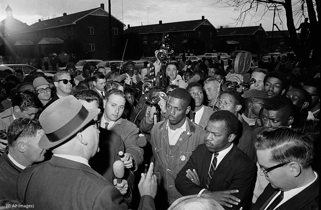John Lewis (right, arms folded) before a twilight march in Selma, Alabama, on February 23, 1965 (© AP Images)