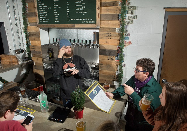 Bartender Zane Pedersen signs with customers Hollie Fallstone (center) and Kate Fetzer (right) at Streetcar 82 Brewing Company in Maryland. (State Dept./D.A. Peterson)