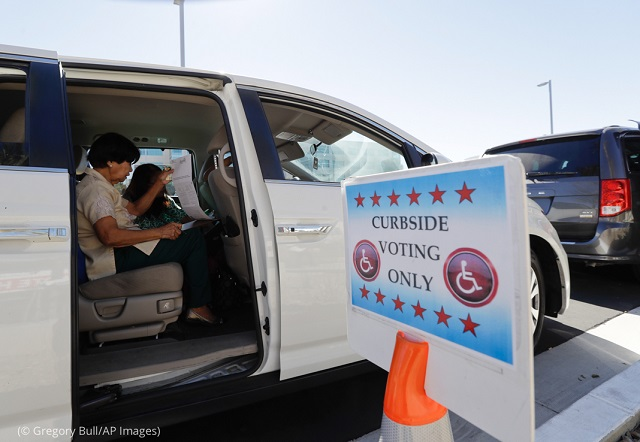 Felicita Subhita reviews her ballot as she votes curbside in San Diego. (© Gregory Bull/AP Images)