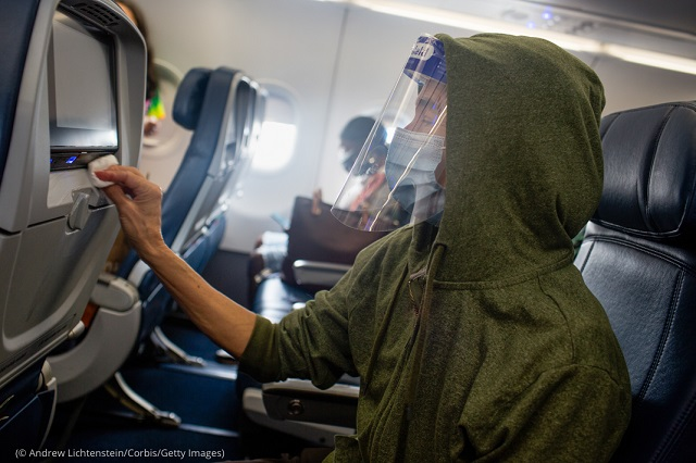 A passenger cleans the seatback before a flight in New York August 8. (© Andrew Lichtenstein/Corbis/Getty Images)