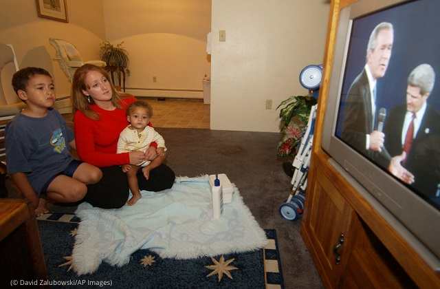 Denver voter Teresa Natale, holding her baby and with her 6-year-old son, watches a 2004 presidential debate. (© David Zalubowski/AP Images)