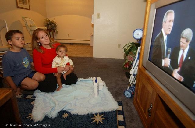 2004年の大統領候補討論会のテレビ中継を見るデンバー在住の有権者 (© David Zalubowski/AP Images)