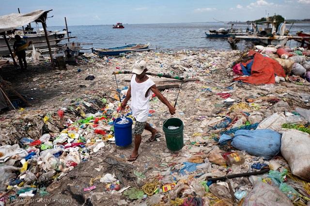 フィリピン・マニラでプラスチックごみに覆われたビーチで魚を運ぶ男性。2018年4月18日 (© Jes Aznar/Getty Images)