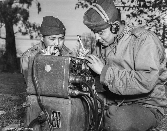 Preston Toledo and his cousin Frank Toledo, Navajo Code Talkers and U.S. Marines, relay orders over a field radio on July 7, 1943. (© PhotoQuest/Getty Images)