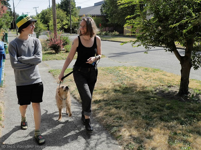 Seattle resident Jennifer Haller, right, was among the first Americans to receive a trial dose of a COVID-19 vaccine. Haller, shown walking with her son Hayden and their dog, encourages others to join vaccine trials. (© Ted S. Warren/AP Images)