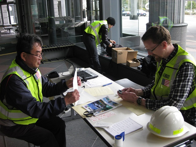 Part of the consular field team sent to Miyagi Prefecture after the earthquake and tsunami, Hitoshi Sekino (left), Andy Utschig (right), and Yoshie Ushimaru (background), set up a makeshift post to help Americans at the Sendai International Center. (Photo courtesy of Ed Burleson)