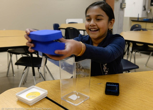 飲み水に含まれる鉛を検知する装置を見せるラオさん。コロラド州ハイランズランチの学校にて2017年11月撮影 (© Kathryn Scott/Denver Post/Getty Images)