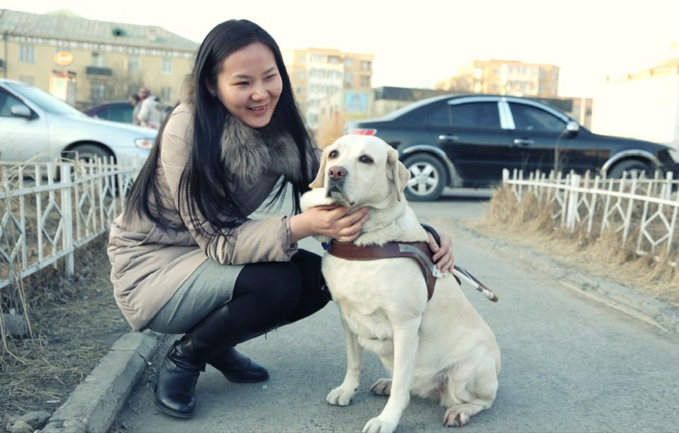 ウヤンガさんと最初の盲導犬「グラディス」。2014年、ウランバートル市立図書館の前で