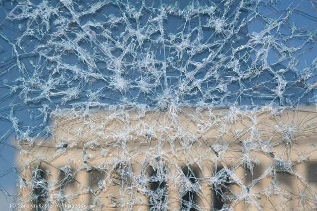 「ガラスの天井を打ち破るカマラ・ハリス副大統領」のクローズアップ。リンカーン記念館がガラスの向こう側に見える。2021年2月、ワシントンにて (© Carolyn Kaster/AP Images)