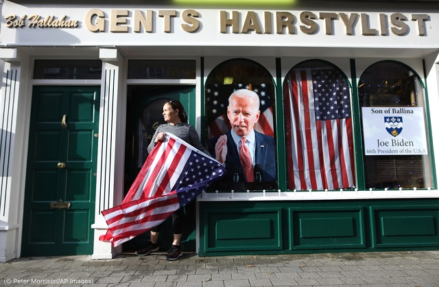 2020年11月7日、ジョー・バイデン氏の大統領当選祝賀会の前に、アイルランドのバリナで星条旗を掲げるキャサリン・ハラハンさん (© Peter Morrison/AP Images)