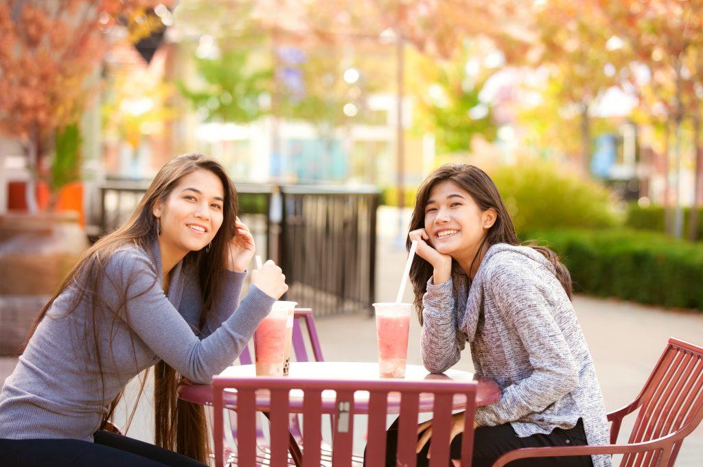 野外のカフェでボバを楽しむ学生 (Jaren Jai Wicklund/Shutterstock.com)