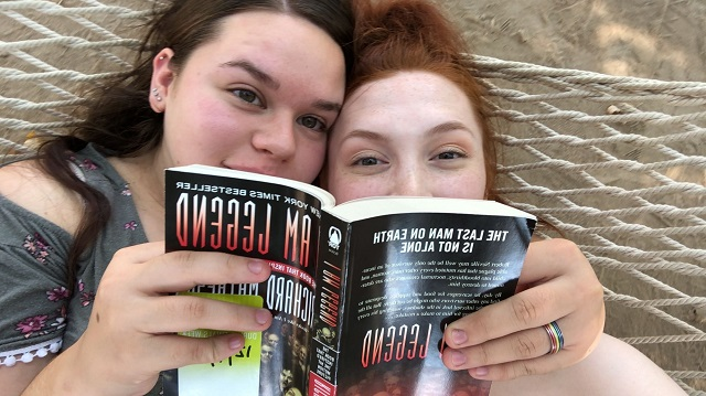 Sophia and her girlfriend reading a book for class on the campus hammocks.
