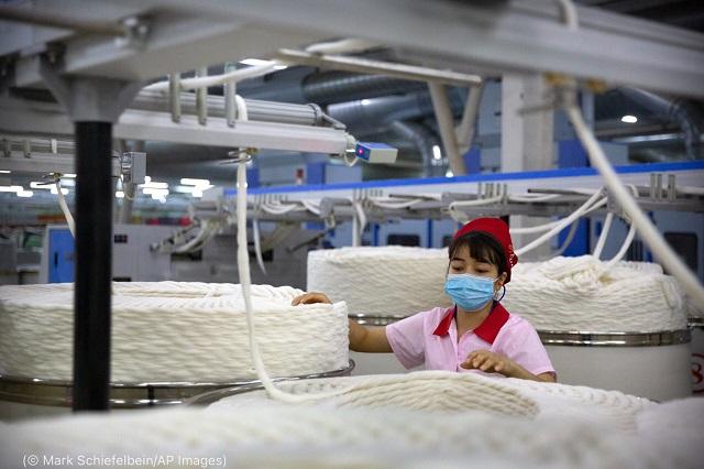 中国・新疆地区の工場で綿糸を処理する労働者。アメリカ政府は強制労働の証拠から、同地区からの綿の輸入を禁止している。 2021年4月20日 (© Mark Schiefelbein/AP Images)