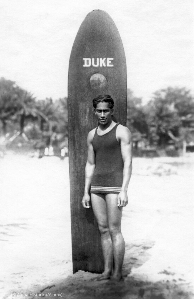 Kahanamoku poses on a Hawaiian beach with his wooden surfboard, circa 1912. (© Alpha Historica/Alamy)