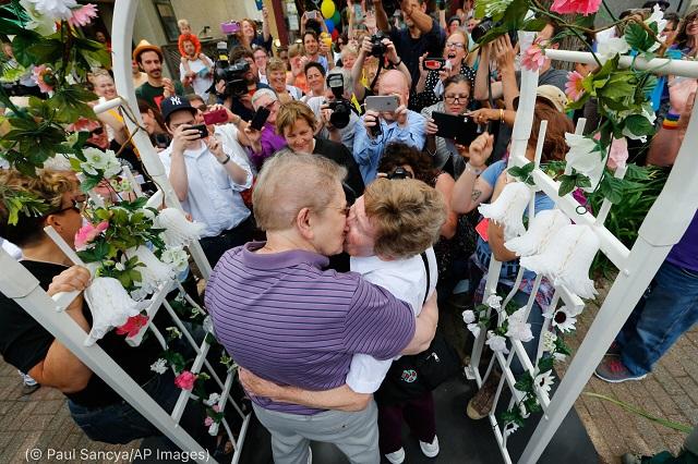 2015年6月、全国での同性婚禁止を破棄した連邦最高裁判所の判決を受け、ミシガン州アナーバーで結婚の誓いを交わし抱き合う43年来のカップル、アン・ソレル(左)とマージ・エイデ(右) (© Paul Sancya/AP Images)