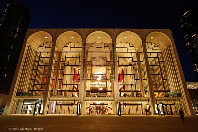 夕暮れにライトアップされるニューヨーク、リンカーンセンターのメトロポリタン歌劇場。今月、観客を入れて公演を再開する (© Kathy Willens/AP Images)