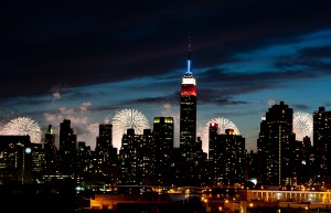 In New York, fireworks explode over the Hudson River behind the Empire State Building, lit red, white and blue for the Fourth of July. (Kathy Kmonicek/AP Images)